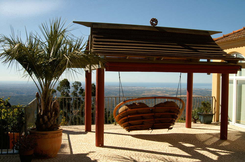 A Circa double hanging outdoors in the garden of a house on a hill, in an exotic location with a breath-taking view