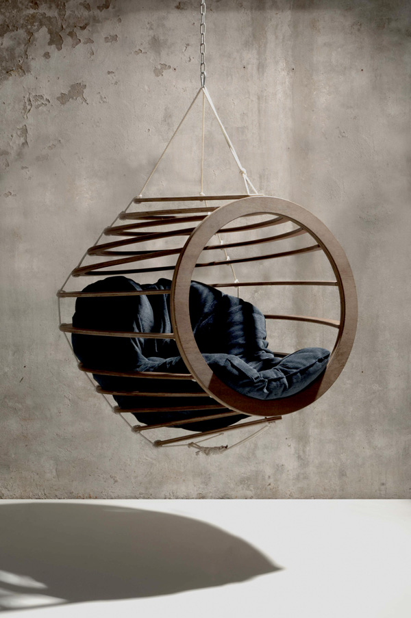 A Hive chair, suspended in the air, hanging off a chain, a wall in the background, a stark industrial setting with cracking paint and columns, the floor, imaculate white and smooth.