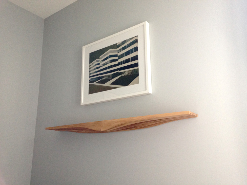 A pair of natural wood coloured contour shelves holding nothing but the air above them, with a framed print hung above them on a grey wall.