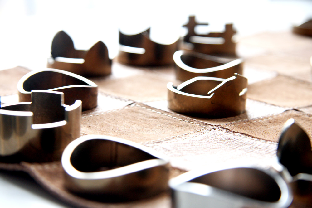 Close-up of raw studio's chess set and leather board